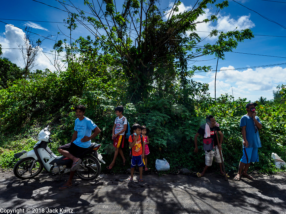 "22 JANUARY 2018 - CAMALIG, ALBAY, PHILIPPINES: People who live on the slopes of Mayon volcano wait for a ride out of the area after the a large eruption in the volcano Monday. There were a series of eruptions on the Mayon volcano near Legazpi Monday. The eruptions started Sunday night and continued through the day. At about midday the volcano sent a plume of ash and smoke towering over Camalig, the largest municipality near the volcano. The Philippine Institute of Volcanology and Seismology (PHIVOLCS) extended the six kilometer danger zone to eight kilometers and raised the alert level from three to four. This is the first time the alert level has been at four since 2009. A level four alert means a ""Hazardous Eruption is Imminent"" and there is ""intense unrest"" in the volcano. The Mayon volcano is the most active volcano in the Philippines. Sunday and Monday's eruptions caused ash falls in several communities but there were no known injuries.    PHOTO BY JACK KURTZ"