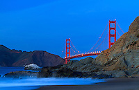 The Golden Gate Bridge in San Francisco as viewed from Marshall Beach as the night slowly makes its way in as the evening waves crash over the rocks on the beach