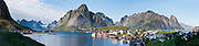 Fog from the Norwegian Sea (part of the North Atlantic Ocean) flows over mountains towards the sunny fishing village of Reine on Moskenesøya (the Moskenes Island), in the Lofoten archipelago, Nordland county, Norway. Panorama stitched from 13 overlapping photos.