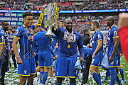 AFC Wimbledon striker Lyle Taylor (33) and AFC Wimbledon striker Adebayo Akinfenwa (10) lift the trophy during the Sky Bet League 2 play off final match between AFC Wimbledon and Plymouth Argyle at Wembley Stadium, London, England on 30 May 2016.