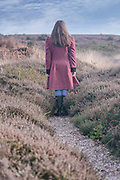 a woman in a red coat is standing on a path in the heather in winter