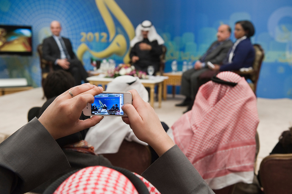 "A member of the audience taking a picture with his mobile phone of a panel of speakers during a Jan. 22 seminar in Kuwait City entitled ""Youth and Arab Political Movement"" which was organized by the Ministry of Information and moderated by Yousef Abdel-Hamid Al-Jassim, a TV presenter and Chief Executive Officer of Six by Six Multimedia Services Co. The ministry is organizing several seminars that shed light on the Gulf Arab country and its democratic tradition in the run up to February 2, 2012 parliamentary elections."