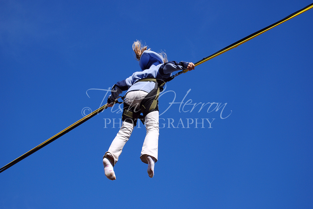 A girl rides high against a blue sky on a bungee jumping ride.