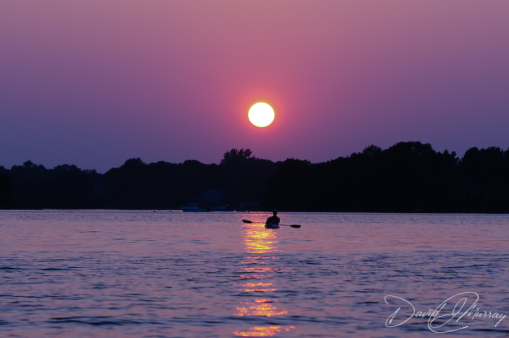 Kayaker watches sun set in purple sky over Portsmouth, NH