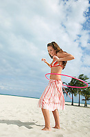 Teenage girl (16-17) playing with hoola hoop on beach