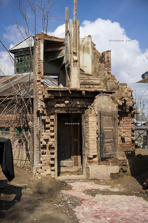 (Alison Griffin to fill in names) (Name)'s three storied house was severely damaged during the floods in September in Abikarpora village on the Dal Lake, Srinagar, Jammu and Kashmir, India, as seen here on 25th March 2015. Since the flood, she has been widowed, and is left with four young children and no home. Her family now lives in a temporary shelter built using the emergency shelter kit, and continues their recovery with the help of relief kits such as education kit, food basket, hygiene kit and non-food items from Save the Children. Photo by Suzanne Lee for Save the Children