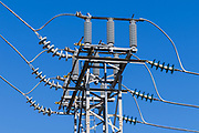High voltage three phase electricity power lines and insulators on a metal tower in a urban substation <br />