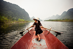 A vietnamese woman rows a barge one the Day River, on her way towards the Perfume Pagoda, Vietnam, Southeast Asia