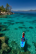 Woman stand up paddle boarding on the crystal clear blue waters of Lake Tahoe in Incline Village, Nevada, North America.