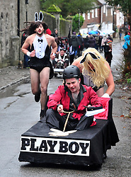 © Licensed to London News Pictures.01/01/2018<br /> SUTTON VALENCE, UK.<br /> PLAYBOY TEAM OUT IN FRONT, WENT ONTO WIN. Josh Davies trying to catch up to his team.<br /> The traditional New Years day Sutton Valence Pram Race in Kent continued this year. In its 38th year the Race was struck by tragedy last year when competitor Francis 'Titch' O' Sullivan tipped over in his spitfire pram and hit his head on the curb, he passed away a day later. A coroners court reported he was not wearing a helmet.<br />  All babies in the pram's have to wear a helmet and the pushers must have contact with the pram and the ground at all times.<br />  <br /> Photo credit: Grant Falvey/LNP