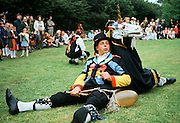 Traditional English Morris Man in costume as The Fool alongside the unicorn at a Morris dancing festival in Cambridge, UK