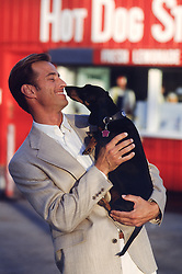 man enjoying kisses by his dog