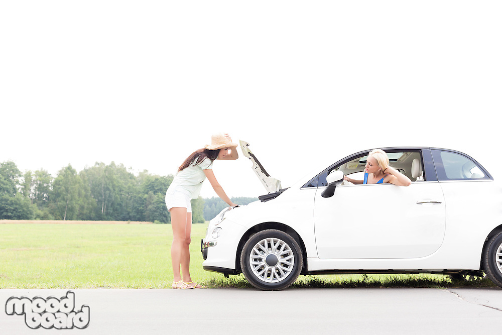 Woman looking at female friend repairing broken down car on country road