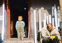 "China, Beijing, 2001. A boy surveys his ""hutong,"" or traditional neighborhood. These low-slung communities are fast disappearing, as streets are widened, and concrete and steel construction replaces bricks in cities all over China.."