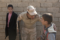 Licensed to London News Pictures. 11/11/2016. Mosul, Iraq. A soldiers, belonging to the Iraqi Army's 9th Armoured Division, talks to a young boy who is asking for food during a visit to Mosul's Hay Intisar district on the south east of the city. The district was taken by Iraqi Security Forces (ISF) around a week ago and, despite its proximity to ongoing fighting between ISF and ISIS militants, many residents still live in the settlement.<br /> <br /> The battle to retake Mosul, which fell June 2014, started on the 16th of October 2016 with Iraqi Security Forces eventually reaching the city on the 1st of November. Since then elements of the Iraq Army and Police have succeeded in pushing into the city and retaking several neighbourhoods allowing civilians living there to be evacuated - though many more remain trapped within Mosul.  Photo credit: Matt Cetti-Roberts/LNP