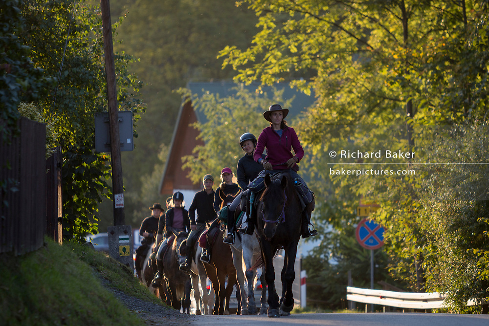 Riders and horses return to the nearby Stadnina Koni Rajd stables after a ride in surrounding countryside, on 21st September 2019, in Jaworki, near Szczawnica, Malopolska, Poland.