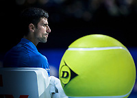 Tennis - 2019 Nitto ATP Finals at The O2 - Day One<br /> <br /> Singles Group Bjorn Borg: Novak Djokovic vs. Matteo Berrettini<br /> <br /> Novak Djokovic (Serbia) sits behind the large Dunlop logo tennis ball <br /> <br /> COLORSPORT/DANIEL BEARHAM