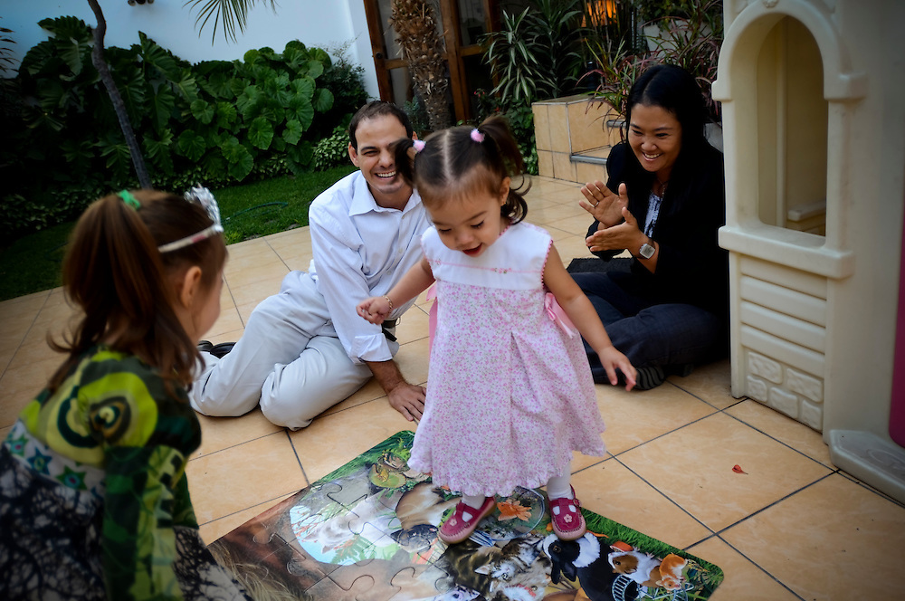 Keiko Fujimori and her husband, Mark Vito Villanella, play with their daughters Kyara Sofía and Kaori Marcela as a photo op for visiting journalists on Easter Sunday.  Fujimori, daughter of Alberto Fujimori, former president currently imprisoned for human rights abuses, has pledged to follow in her father's footsteps, taking a heavy hand on crime, but also to improve social programs.