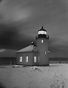 Alki Point Lighthouse stands a solitary vigil on wintry evenings, its windows aglow in contrast to the snow all around and the off-stormy sea beyond. (Josef Scaylea / The Seattle Times, 1950)