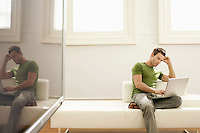 Pensive man using laptop on modern sofa in modern apartment