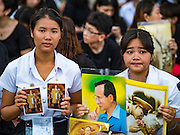 20 OCTOBER 2016 - BANGKOK, THAILAND: School girls on Sanam Luang hold up photos of Bhumibol Adulyadej, the King of Thailand, while they mourn the death of the King. Sanam Luang, the Royal Ceremonial Ground, is packed with people mourning the Monarch's death. The King died Oct. 13, 2016. He was 88. His death came after a period of failing health. Bhumibol Adulyadej was born in Cambridge, MA, on 5 December 1927. He was the ninth monarch of Thailand from the Chakri Dynasty and is also known as Rama IX. He became King on June 9, 1946 and served as King of Thailand for 70 years, 126 days. He was, at the time of his death, the world's longest-serving head of state and the longest-reigning monarch in Thai history.        PHOTO BY JACK KURTZ