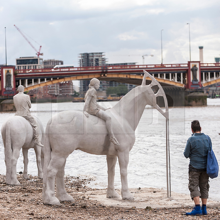 "© Licensed to London News Pictures. 02/09/2015 London, UK. A man walks by the art installation entitled ""The Rising Tide"" (comprising four horse-riders on horses with petroleum pumps for heads) by the underwater eco-sculptor Jason deCaires Taylor, which stands on the foreshore of the River Thames in Vauxhall and is revealed with each low tide.  The installation aims to question man's reliance on fossil fuels and is part of this year's Totally Thames festival. Photo credit : Stephen Chung/LNP"