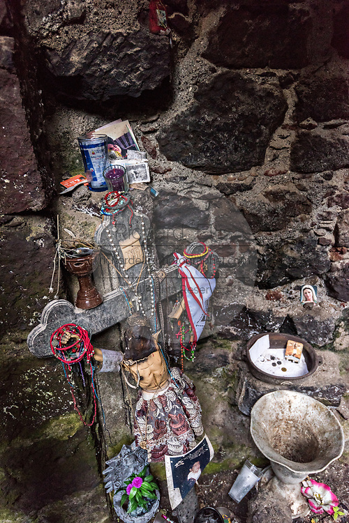 Religious objects left behind in the ruins of the naive in the San Juan Parangaricutiro church partly buried in a sea of dried lava rock in the remote village of San Juan Parangaricutiro, Michoacan, Mexico. This church is the only remaining structure left buried in the eight-year eruption of the Paricutin volcano which consumed two villages in 1943 and covered the region in lava and ash.