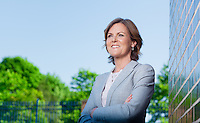 Corporate portrait taken outdoors with blue sky background featuring business woman looking into the distance