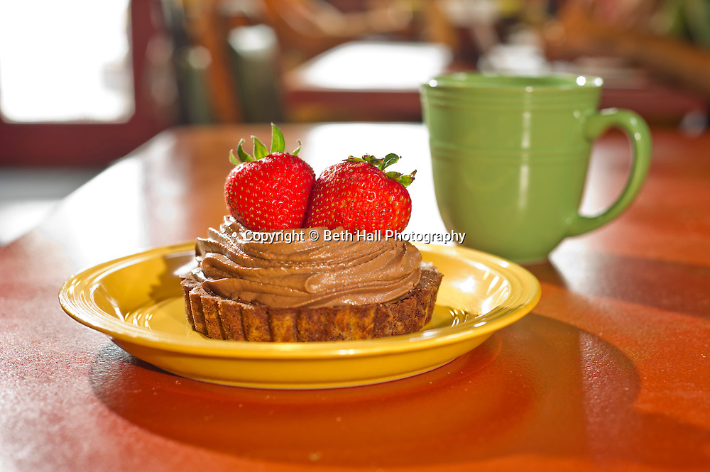 A chocolate tart with strawberries and coffee on a plate at a bakery.