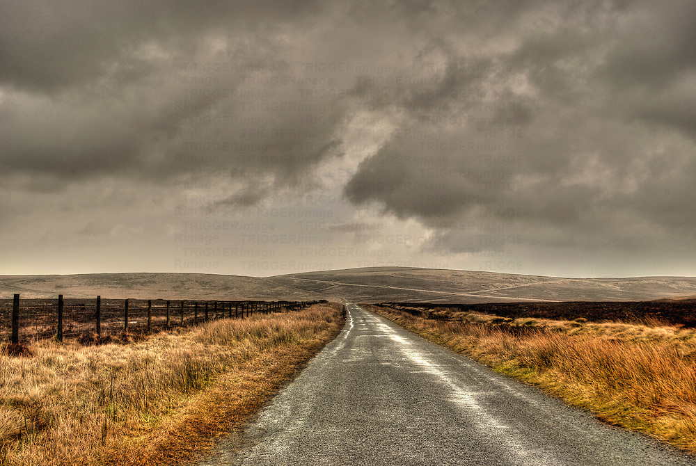 Deserted road disappearing into distance under grey sky