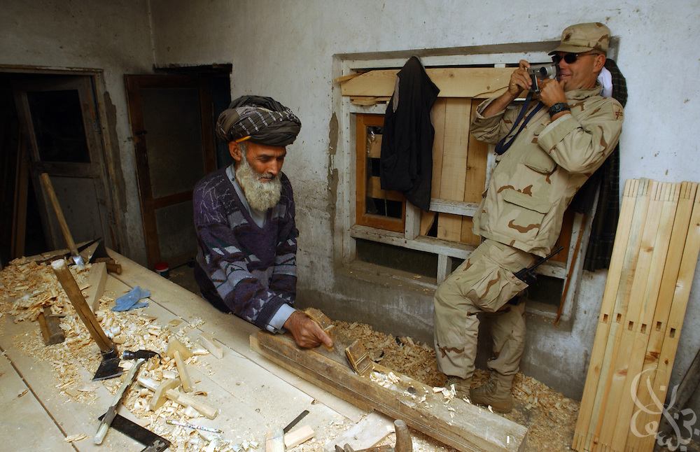 U.S. Army Maj. Bryan Cole, from the 489th Civil Affairs Batallion based in Knoxville, TN, photographs an Afghan carpenter May, 26, 2002 at the Parwan Institute for Teachers Training in Charikar, Afghanistan. The 489th Civil Affairs division delivered a load of blankets to the institute for students returning to the dorms and classes next week.