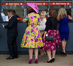 LIVERPOOL, ENGLAND - Friday, April 4, 2014: Racegoers placing bets during Ladies' Day on Day Two of the Aintree Grand National Festival at Aintree Racecourse. (Pic by David Rawcliffe/Propaganda)