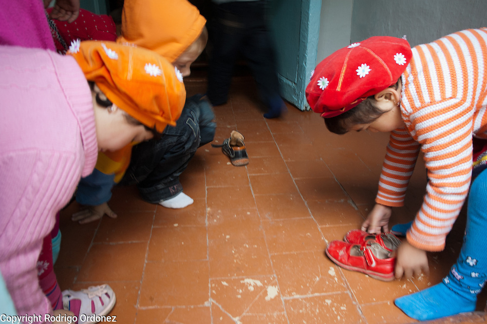 Children remove their shoes before entering the main building of Kindergarten 29, in Osh (Kyrgyzstan), where Save the Children supports a child-friendly space.