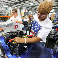Annie Gipson, right, and Mendy Mayo, technicians at Pride Mobility, work on installing the batteries and the cover onto the Victory 10 on Thursday.