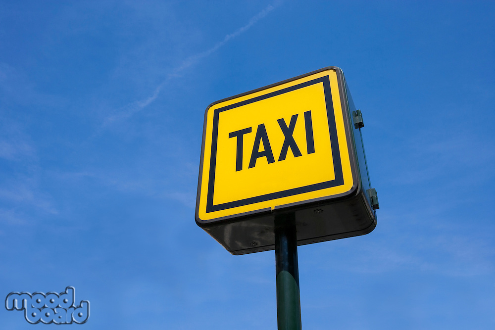 Low angle view of taxi sign against blue sky