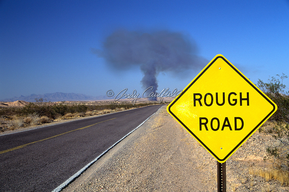 """Rough Road"" ahead, yellow highway sign in front of mushroom shaped smoke cloud on road in western US"