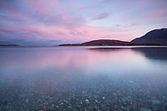 A glowing dawn meets a flat calm Ardmair Bay, just north of Ullapool in the northwest of Scotland.