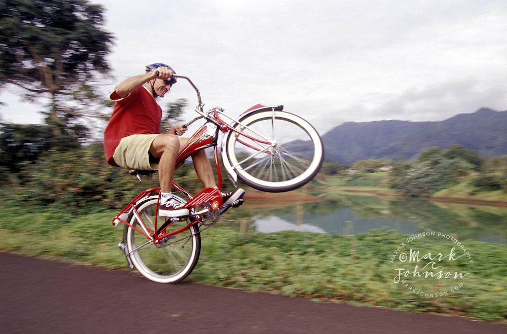 Man pulling a wheely on his cruiser bike, Kauai, Hawaii