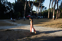 "ROME, ITALY - 3 JULY 2016: A woman walks in the Ponte Nomentano park which hosts the iFest, an alternative music festival, where the Gipsy Queens have a food stand, in Rome, Italy, on July 3rd 2016.<br /> <br /> The Gipsy Queens are a travelling catering business founded by Roma women in Rome.<br /> <br /> In 2015 Arci Solidarietà, an independent association for the promotion of social development, launched the ""Tavolo delle donne rom"" (Round table of Roma women) to both incentivise the process of integration of Roma in the city of Rome and to strengthen the Roma women's self-esteem in the context of a culture tied to patriarchal models. The ""Gipsy Queens"" project was founded by ten Roma women in July 2015 after an event organised together with Arci Solidarietà in the Candoni Roma camp in the Magliana, a neighbourhood in the South-West periphery of Rome, during which people were invited to dance and eat Roma cuisine. The goal of the Gipsy Queen travelling catering business is to support equal opportunities and female entrepreneurship among Roma women, who are often relegated to the roles of wives and mothers."
