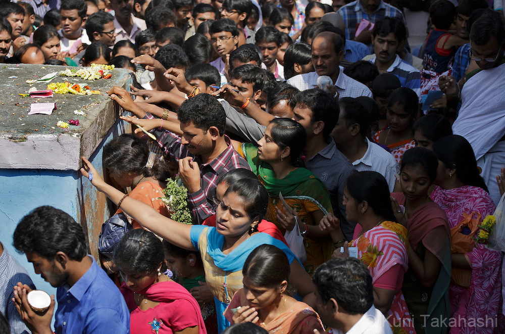 Hindu devotees walk around and touch the shrine at the Chilkur Balaji Temple in Chilkur, about 30km west of Hyderabad, India on Nov 2, 2014. The temple, known as Visa God, has acquired a reputation that the deity here is particularly powerful in granting an visa. During the visit, the devotee goes through circumambulations of the inner shrine and makes a vow. If they get their visa, they return to the temple, and fulfill their vow, which is to walk 108 times around the temple. <br /> (Photo by Kuni Takahashi)