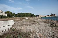 Brindisi, Castello (Alfonsino) Aragonese.<br /> Il castello alfonsino (detto anche Castel Rosso dal colore dei conci di carparo usati per la sua costruzione, o castello di Mare) è una complessa opera fortificata costruita sull'isola di Sant'Andrea, all'imboccatura del porto esterno di Brindisi. Il castello è contiguo al Forte a mare, i cui lavori di costruzione, iniziati nel 1558, regnante Filippo II d'Austria, figlio di Carlo V, durarono ben 46 anni.<br /> <br /> Il castello alfonsino occupa il promontorio meridionale con forme irregolari che seguono la conformazione del luogo (ha subito anche crolli e ricostruzioni): all'interno è un salone decorato da un lavabo con stipiti in pietra (XVI secolo). Alla fine del XV secolo risalgono i due baluardi, rotondo quello verso l'interno, triangolare quello verso il mare aperto.<br /> Caratteristico è il suo piccolo porto interno, cui si accede per un archivolto aperto nelle mura che verso il 1577 congiunsero le costruzione aragonese all'ampliamento spagnolo. Da una parte la struttura fortificata quattrocentesca con un portale; dall'altra la cosiddetta Opera a corno che segue i dettami dell'architettura fortificata cinquecentesca. Anche questa parte è preceduta da un portale adorno di stemmi.<br /> L'isola è saldata alla sponda ovest da una diga che chiude la Bocca di Puglia, mentre tra l'isola e la sponda sud si protendono due dighe che restringono l'imboccatura del porto a 250 metri.<br /> <br /> L'isola era occupata almeno dal XI secolo dall'antica abbazia benedettina di Sant'Andrea all'Isola (pochissimi i resti, in particolare capitelli, visibili al Museo archeologico provinciale Francesco Ribezzo di Brindisi), che però fu abbandonata dopo gli eventi che sconvolsero la città (XIV-XV secolo). Alfonso V d'Aragona nel 1445 decise così di costruire una prima torre, sorta come avamposto difensivo del porto all'estremità dell'isola; l'opera venne poi prolungata verso NE nel 1481 (castello alfonsino).<br /> Dal 1558 al 1604 buo