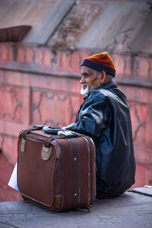 Man and suitcase, in front of the Friday Mosque (Delhi, India, 2011).