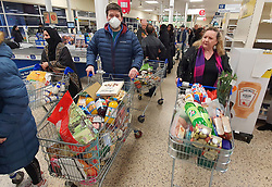 © Licensed to London News Pictures. 18/03/2020. London, UK. A shopper in a face mask queues with others for the checkouts at 06:30am in a south London Tesco after the store closed overnight to re-stock and open at 6am. The government has announced £350 billion in loans will be available for UK businesses as the virus takes hold.  Photo credit: Peter Macdiarmid/LNP