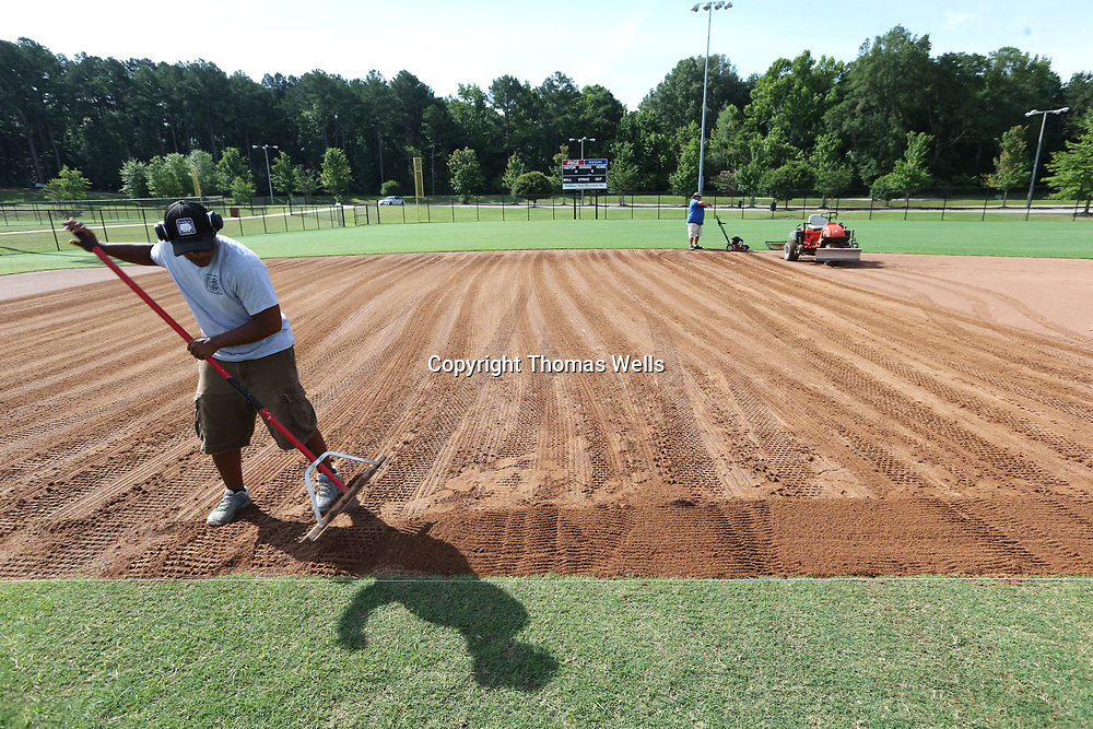 """After dragging the most of the infield Josh Patterson uses the lose dirt to fill up the """"10th man"""" where dirt erodes from the edge of the infield grass and creates a small drop off thats causes the a hit ball to take unny hops."""