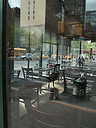 A complicated composition of reflections, the interior of a corner restaurant, and the traffic on 57th  Street seen through the windows on two sides of the restaurant.