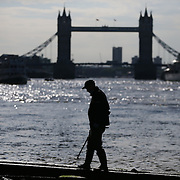 Mudlarker Matthew Goode uses a metal detector to look for items near Tower Bridge on the bank of the river Thames in London, Britain May 23, 2016. When the river Thames is at low tide, mudlarkers scour the shore for historical artefacts and remains from there City of London's ancient past. Finds can date back to Roman times to when the city was found up until more recent times. Anyone can walk along the river and look for finds, but the uses of metal detectors and digging is restricted. Mudlarkers need to be licences by the Port of London Authority. All find should be register with the Museum of London. REUTERS/Neil Hall