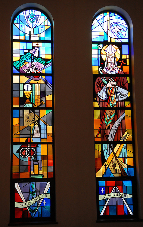 Two stained glass panels inside Our Lady Queen of Peace Church in Milwaukee depict the sacraments and St. Adalbert. (Photo by Sam Lucero)