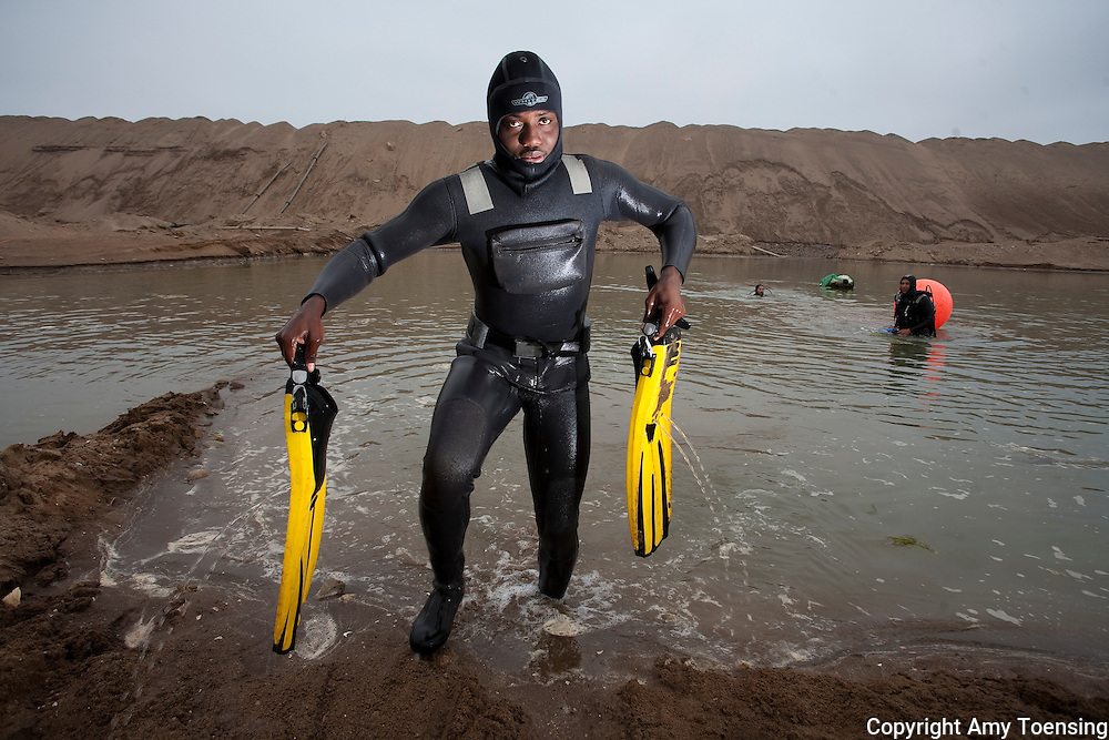 ORANJEMUND, NAMIBIA -- OCTOBER 07: Namdeb Divers work to recover a broken pump at the base of the seawall that holds the ocean back from the site of the Oranjemund shipwreck on October 07, 2008 in Oranjemund, Namibia. The wreck was discovered by miners in the Namdeb diamond mine off the coast of Namibia. The ship was found seven meters below sea level on April 1, 2008. Archeologists presume the wreck is from the early 1500s. Most of the the artifacts found are being stored in a storage shed at the Namdeb Diamond Mine. Items include: copper ingots, bronze canons, canon balls, pewter bowls and plates, ivory tusks from African elephants, and most substantial over 2000 gold coins- approximately 21 kg - the most gold found in Africa since the Valley of the Kings in Egypt. (Photo by Amy Toensing) _________________________________<br /> <br /> For stock or print inquires, please email us at studio@moyer-toensing.com.
