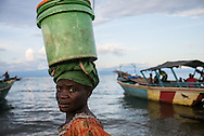 DRC / Burundi Refugees / A woman is seen in Mboko beach carring good  on her head after landing from a boat arriving from Burundi. Among the passengers more 50 Burundian refugees were onboard.<br /> More than 9000 Burundians refugees have crossed into the DRC over the past few weeks. The new<br /> arrivals are being hosted by local families, but the growing numbers are straining<br /> available support.  Work is ongoing to identify a site<br /> where all the refugees can be moved, and from where they can have access to<br /> facilities such as schools, health centers and with proper security. / UNHCR / F.Scoppa / May 2015