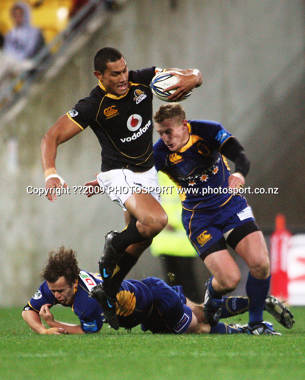 Wellington centre Robert Fruean skips out of the tackle of Andrew Parata as Brett Mather closes in.<br /> Air NZ Cup Ranfurly Shield match - Wellington Lions v Otago at Westpac Stadium, Wellington, New Zealand. Friday, 31 July 2009. Photo: Dave Lintott/PHOTOSPORT